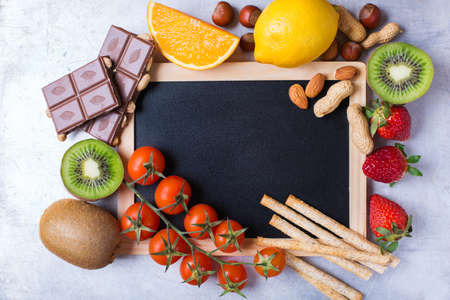 Selection of allergy food, orange lemon citrus fruit red tomato strawberry kiwi chocolate nuts bread gluten food. Copy space board background, top view flat lay overhead