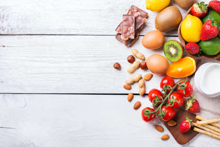 Selection of allergy food, orange citrus juice milk red tomato strawberry kiwi eggs chocolate nuts bread gluten on a rustic wooden table. Copy space background, top view flat lay overhead Stock Photo