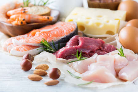 Assortment of healthy protein source and body building food. Meat beef salmon chicken eggs dairy products milk cheese quinoa nuts Stock Photo