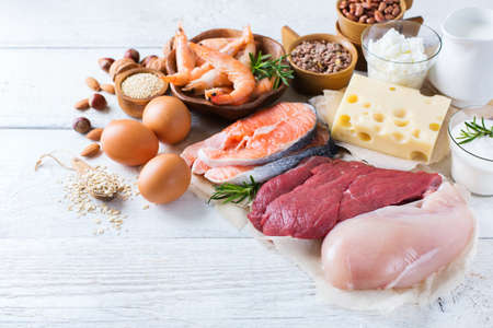 Assortment of healthy protein source and body building food. Meat beef salmon shrimp chicken eggs dairy products milk cheese yogurt beans quinoa nuts oat meal. Stock Photo - 74031453