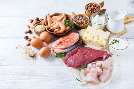 Assortment of healthy protein source and body building food. Meat beef salmon shrimp chicken eggs dairy products milk cheese yogurt beans quinoa nuts oat meal. Copy space background Stock Photo - 74031457