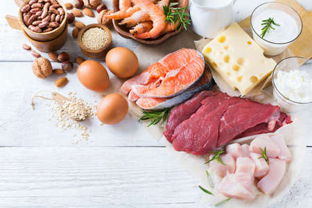 leguminosas: Assortment of healthy protein source and body building food. Meat beef salmon shrimp chicken eggs dairy products milk cheese yogurt beans quinoa nuts oat meal. Copy space background