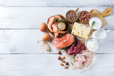Assortment of healthy protein source and body building food. Meat beef salmon shrimp chicken eggs dairy products milk cheese yogurt beans quinoa nuts oat meal. Copy space background, top view Stock Photo