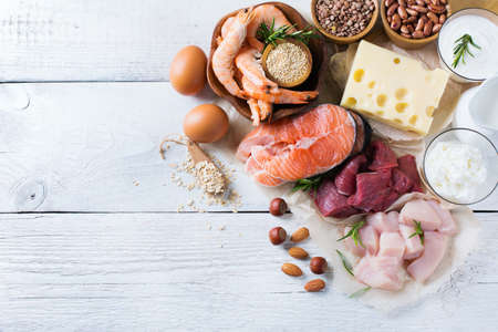 Assortment of healthy protein source and body building food. Meat beef salmon shrimp chicken eggs dairy products milk cheese yogurt beans quinoa nuts oat meal. Copy space background, top view Archivio Fotografico