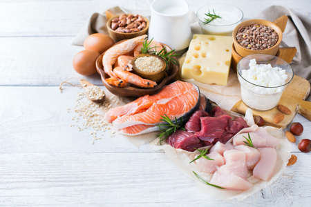Assortment of healthy protein source and body building food. Meat beef salmon shrimp chicken eggs dairy products milk cheese yogurt beans quinoa nuts oat meal. Copy space background Stock Photo - 74070854