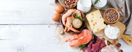 Assortment of healthy protein source and body building food. Meat beef salmon shrimp chicken eggs dairy products milk cheese yogurt beans quinoa nuts oat meal. Top view Stockfoto