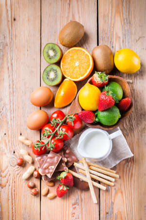 Selection of allergy food, orange citrus juice milk red tomato strawberry kiwi eggs chocolate nuts bread gluten diary products on a rustic wooden table. Top view flat lay Stock Photo