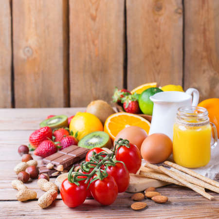 Selection of allergy food, orange citrus juice milk red tomato strawberry kiwi eggs chocolate nuts bread gluten diary products on a rustic wooden table. Copy space background