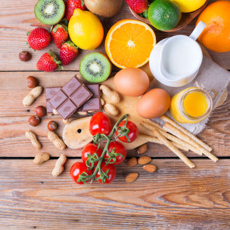 Selection of allergy food, orange citrus juice milk red tomato strawberry kiwi eggs chocolate nuts bread gluten diary products on a rustic wooden table. Copy space background, top view flat lay