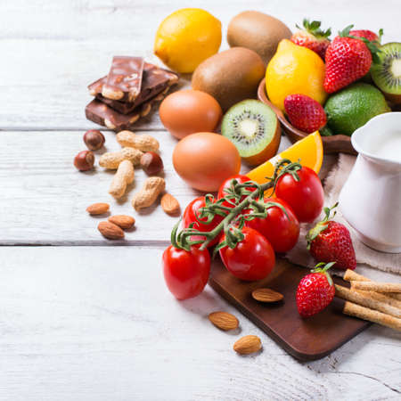 Selection of allergy food, orange citrus juice milk red tomato strawberry kiwi eggs chocolate nuts bread gluten diary products on a white rustic wooden table