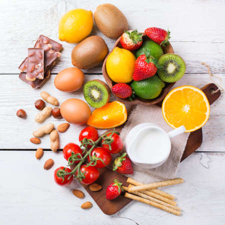 Selection of allergy food, orange citrus juice milk red tomato strawberry kiwi eggs chocolate nuts bread gluten diary products on a white rustic wooden table. Top view flat lay