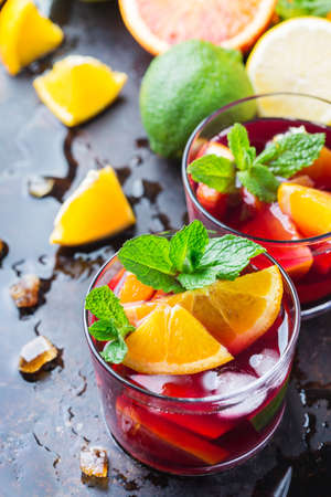 Traditional cold spanish sangria cocktail with red wine and ingredients on a black table, citrus fruit orange lime lemon mint leaves and ice for hot summer days Banque d'images