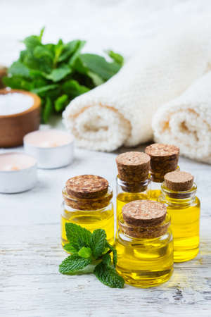 bath essence: Health and beauty, still life spa concept. Assortment of organic essential oil in a small glass jar with green mint leaves towels sea salt candles on a white rustic wooden table