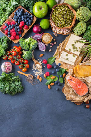 Selection assortment of healthy balanced food for heart, diet, detox, salmon fish, chicken breast, tofu, seeds nuts broccoli green spinach asparagus, berries. Top view flat lay, copy space background Reklamní fotografie