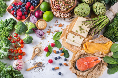 Selection assortment of healthy balanced food for heart, diet, detox, salmon fish, chicken breast, tofu, seeds nuts broccoli green spinach asparagus, berries. Top view flat lay overhead