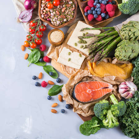 Selection assortment of healthy balanced food for heart, diet, detox, salmon fish, chicken breast, tofu, seeds nuts broccoli green spinach asparagus, berries. Top view flat lay, copy space background Standard-Bild
