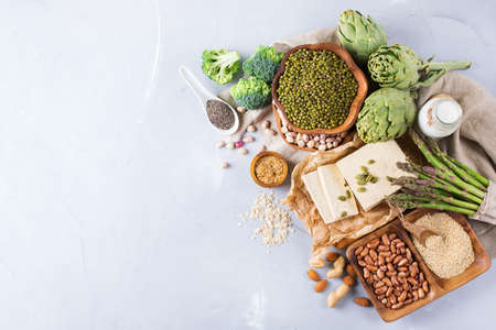 Assortment of healthy vegan protein source and body building food. Tofu soy milk beans asparagus broccoli artichokes almond peanut pumpkin chia flax seeds quinoa oat. Copy space background, top view