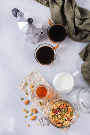Healthy diet nutrition food concept. Homemade muesli granola with honey nuts milk and black coffee for early morning breakfast. Modern minimalism style background, top view flat lay