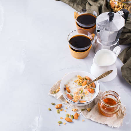 greek pot: Healthy diet nutrition food concept. Homemade muesli granola with honey nuts milk and black coffee for early morning breakfast. Copy space modern minimalism style background Archivio Fotografico