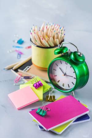Back to school, children education concept. Assortment of supplies, crayons, pens, chalks, alarm clock. Copy space background