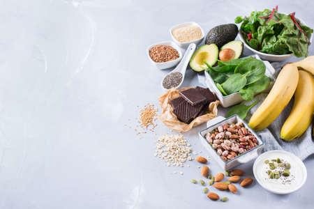 Concept de régime alimentaire sain pour la nutrition alimentaire. Assortiment de sources élevées de magnésium. Chardonnerets au chocolat à la banane, avocat, sarrasin, graines de lin de sésame, yaourt, noix, haricots d'avoine. Fond d'espace de copie Banque d'images - 80499630