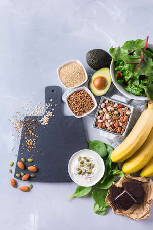 vitamin rich: Healthy food nutrition dieting concept. Assortment of high magnesium sources. Banana chocolate spinach chard, avocado, buckwheat, sesame chia flax seeds, yogurt, nuts, beans oat. Copy space background
