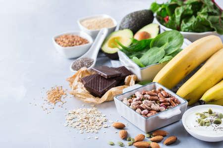 Concetto di dieta nutrizione sana cibo. Assortimento di alte fonti di magnesio. Bietole di spinaci al cioccolato banana, avocado, grano saraceno, semi di lino chia sesamo, yogurt, noci, avena fagioli. Copia lo sfondo dello spazio