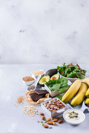 Healthy food nutrition dieting concept. Assortment of high magnesium sources. Banana chocolate spinach chard, avocado, buckwheat, sesame chia flax seeds, yogurt, nuts, beans oat. Copy space background