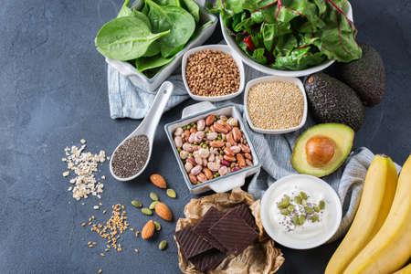 Concetto di dieta nutrizione sana alimentare. Assortimento di sorgenti di magnesio elevato. Chard di spinaci al cioccolato, avocado, grano saraceno, sesamo chia semi di lino, yogurt, noci, fagioli