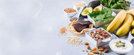 Healthy food nutrition dieting concept. Assortment of high magnesium sources. Banana chocolate spinach chard, avocado, buckwheat, sesame chia flax seeds, yogurt, nuts, beans oat. Copy space background Фото со стока - 80499942