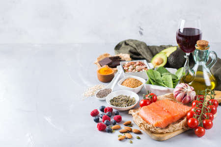 Balanced diet food concept. Assortment of healthy food low cholesterol, spinach avocado red wine green tea salmon tomato berries flax chia seeds turmeric garlic nuts olive oil. Copy space background Stock Photo - 80575501