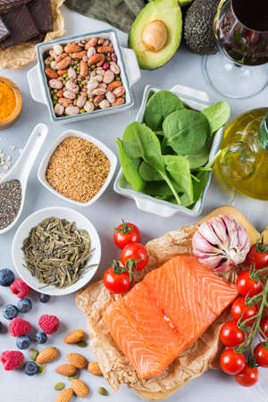 Balanced diet food concept. Assortment of healthy food low cholesterol, spinach avocado red wine green tea salmon tomato berries flax chia seeds turmeric garlic nuts olive oil