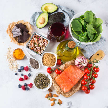 Balanced diet food concept. Assortment of healthy food low cholesterol, spinach avocado red wine green tea salmon tomato berries flax chia seeds turmeric garlic nuts olive oil Banco de Imagens - 80575504