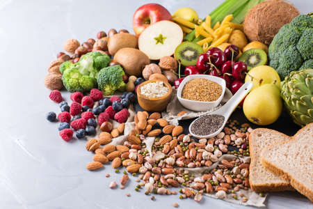 Healthy balanced dieting concept. Selection of rich fiber sources vegan food. Vegetables fruit seeds beans ingredients for cooking. Copy space background