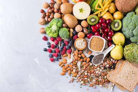 vitamin rich: Healthy balanced dieting concept. Selection of rich fiber sources vegan food. Vegetables fruit seeds beans ingredients for cooking. Copy space background, top view