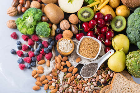 Healthy balanced dieting concept. Selection of rich fiber sources vegan food. Vegetables fruit seeds beans ingredients for cooking. Top view Stock Photo