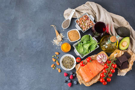 Balanced diet food concept. Assortment of healthy food low cholesterol, spinach avocado red wine green tea salmon tomato berries flax chia seeds turmeric garlic nuts olive oil. Copy space background Stock Photo - 82621992