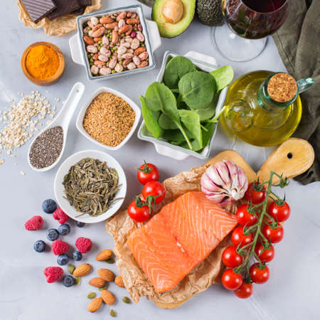 Balanced diet food concept. Assortment of healthy food low cholesterol, spinach avocado red wine green tea salmon tomato berries flax chia seeds turmeric garlic nuts olive oil. Top view 版權商用圖片