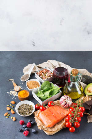 raw: Balanced diet food concept. Assortment of healthy food low cholesterol, spinach avocado red wine green tea salmon tomato berries flax chia seeds turmeric garlic nuts olive oil. Copy space background