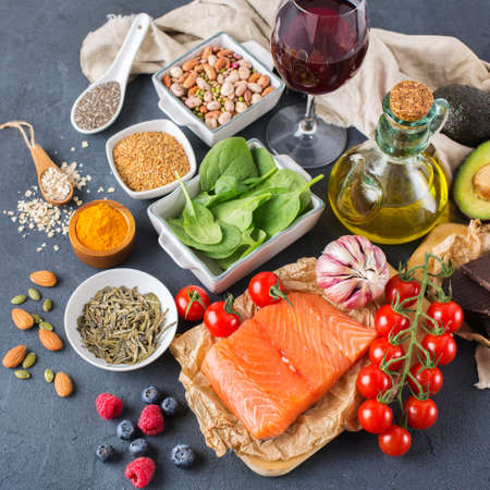 Balanced diet food concept. Assortment of healthy food low cholesterol, spinach avocado red wine green tea salmon tomato berries flax chia seeds turmeric garlic nuts olive oil 写真素材