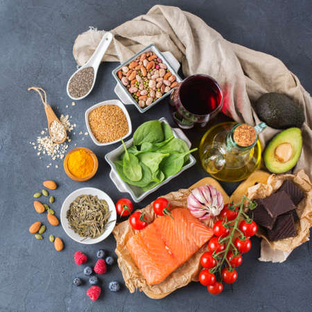 Balanced diet food concept. Assortment of healthy food low cholesterol, spinach avocado red wine green tea salmon tomato berries flax chia seeds turmeric garlic nuts olive oil. Top view Stock Photo