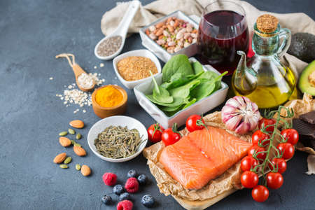 raw: Balanced diet food concept. Assortment of healthy food low cholesterol, spinach avocado red wine green tea salmon tomato berries flax chia seeds turmeric garlic nuts olive oil Stock Photo