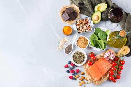 バランスの取れた食事食品のコンセプト。健康食品低コレステロール、ほうれん草アボカド赤ワイン緑茶サーモン トマト果実亜麻嘉種ウコンにんにくナッツ オリーブ オイルの品揃え。スペースの背景をコピーします。 写真素材 - 84218935