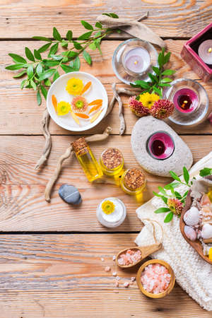 table top: Autumn fall spa still life wellness setting concept. Assortment of essential oil cream sea salt natural soap candles orange flowers and towel on a rustic wooden table. Copy space background, top view