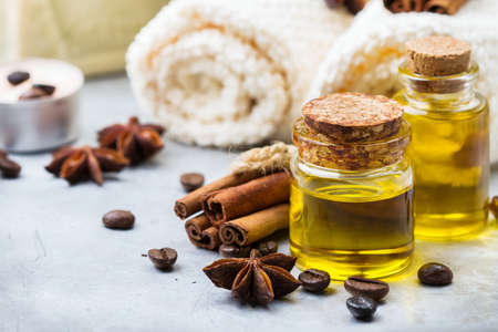 Health and beauty, still life spa concept. Assortment of organic essential oil in a small glass jar with towels candles cinnamon coffee spices on a table
