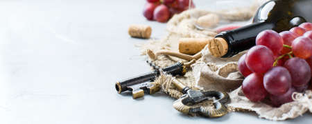 Food and drink, still life, holidays seasonal harvesting fall concept. Bottle, corkscrew, corks, glass of red wine and grapes on a trendy concrete table. Copy space background Stock Photo