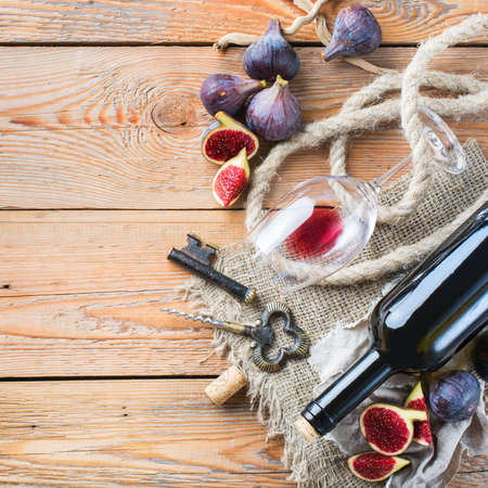 Food and drink, still life, holidays seasonal harvesting fall concept. Bottle, corkscrew, corks, glass of red wine and figs on a rustic wooden table. Copy space background, top view flat lay