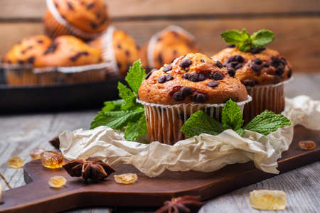 Food and drink, seasonal concept. Homemade chocolate chip muffins with green mint for breakfast on a rustic wooden cutting board. Selective focus
