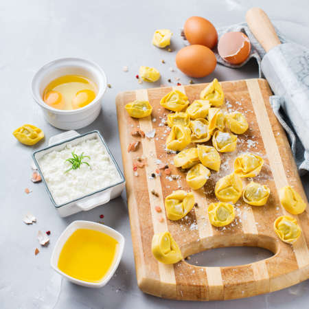 olive green: Assortment of italian food and ingredients, handmade tortellini with ricotta on a table Stock Photo