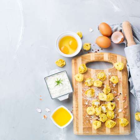 olive green: Assortment of italian food and ingredients, handmade tortellini with ricotta on a table. Top view flat lay, copy space background Stock Photo